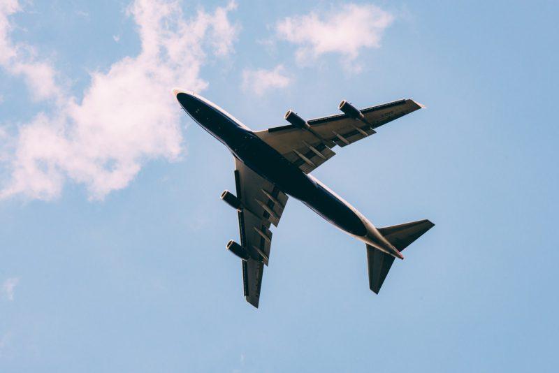 Het silhouet van een vliegtuig tegen een blauwe lucht