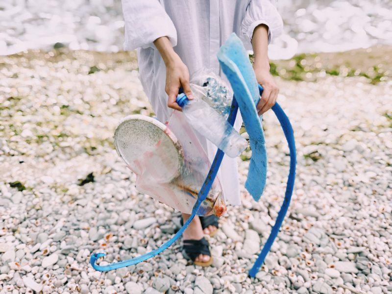 Een persoon op kiezelstenen houdt oude materialen vast: plastic flesje, blauwe plastic slang en blauw piepschuim